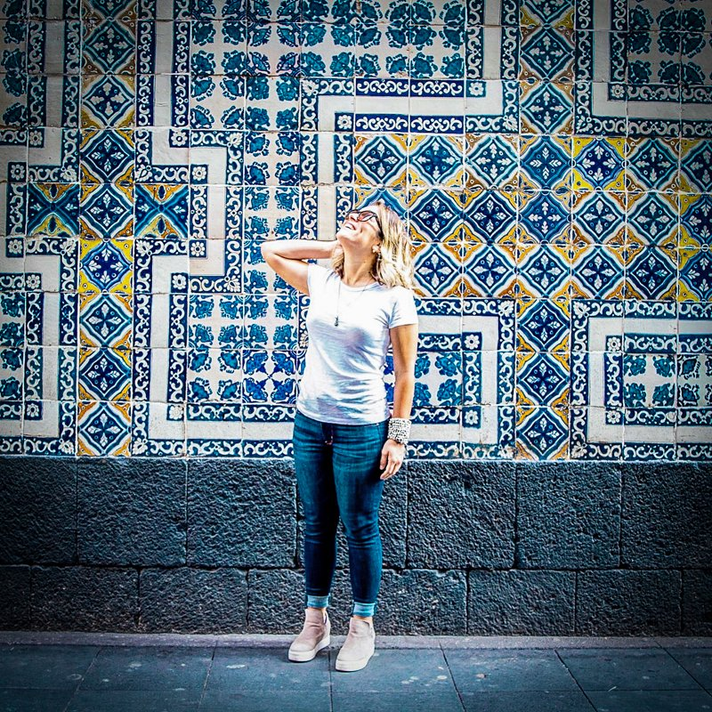 woman in jeans and white tshirt in front of blue tiled building in Mexico City