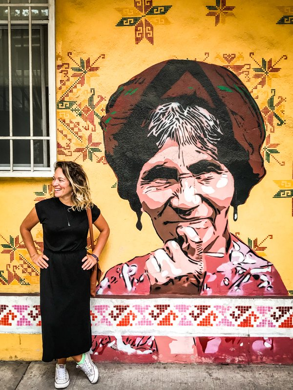 woman standing in front of street art of an old woman in mexico city