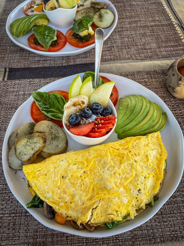 a huge egg omelet with fruit, potatoes, and avocado stuffed with vegetables