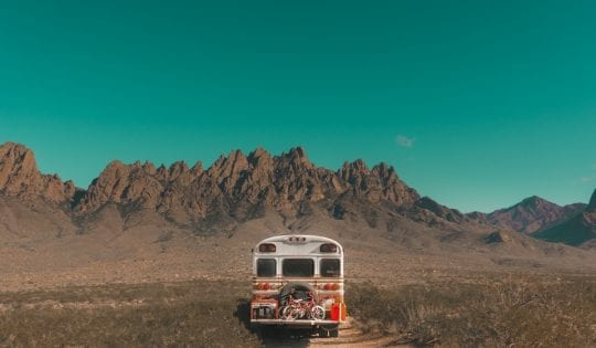 riding a bus on a dirt road
