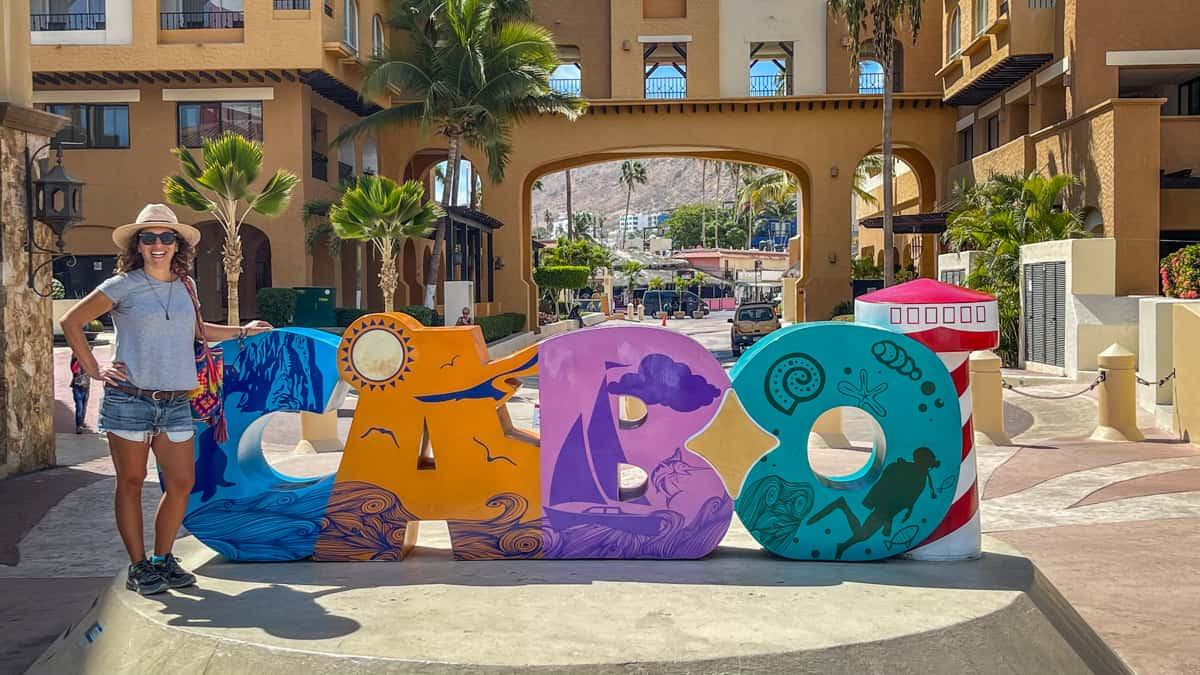 standing in front of the cabo sign in Cabo San Lucas Mexico