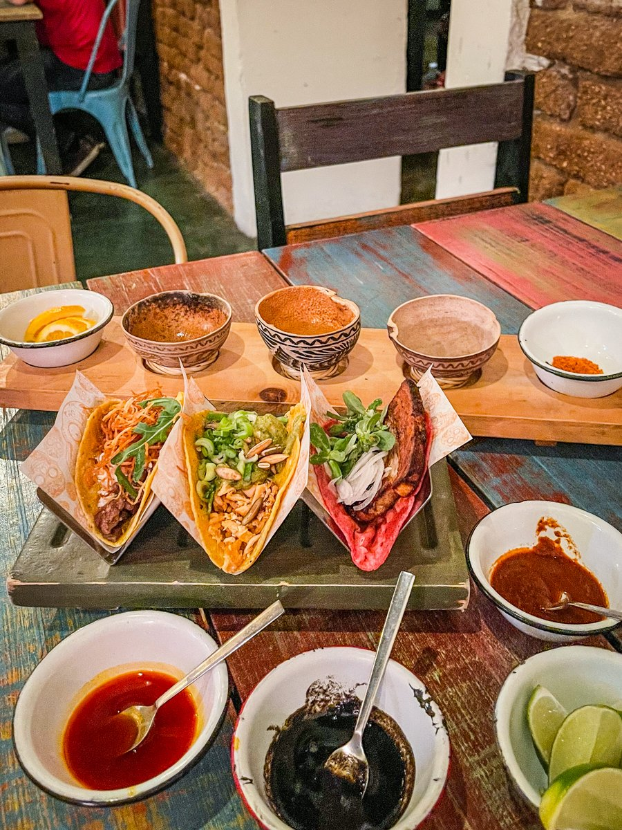 tacos on a table with salsas and mezcal