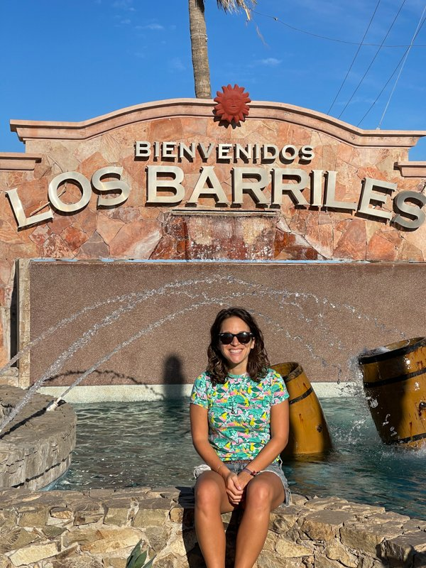 sitting in front of the Los Barriles sign