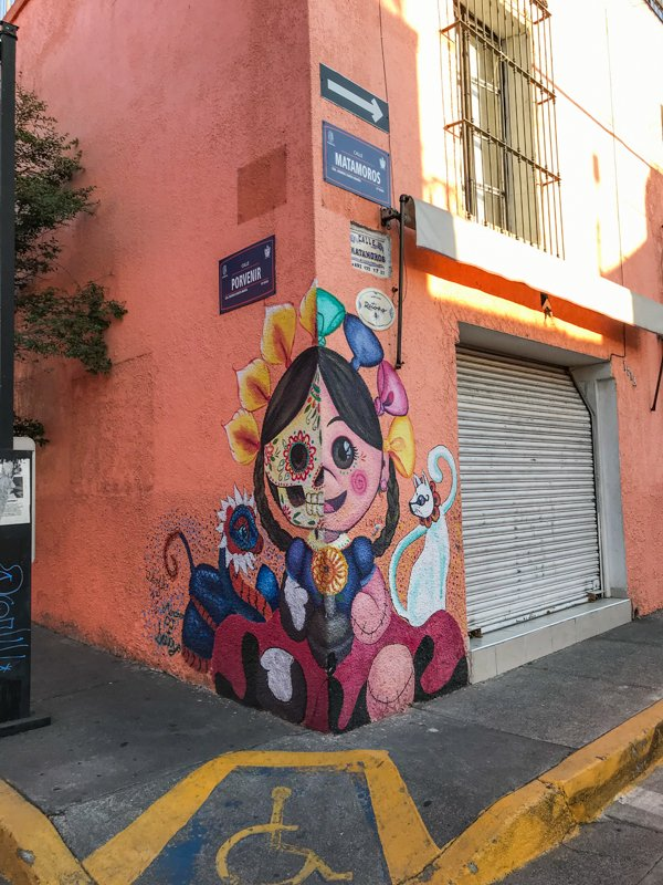 colorful day of the dead street art on a wall.