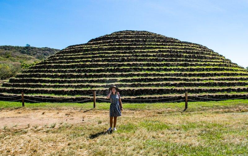woman standing in front of guachimontones in guadalajara mexico