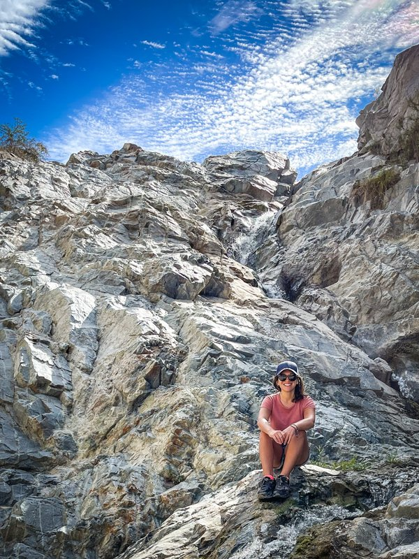 woman sitting on a rock after hiking