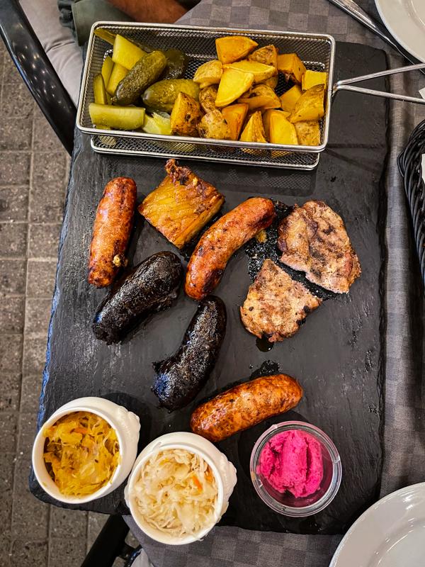 sausages, pork, potatoes, pickles, and sauce on a slate