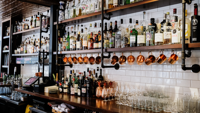 bar with alcohol on wooden shelves