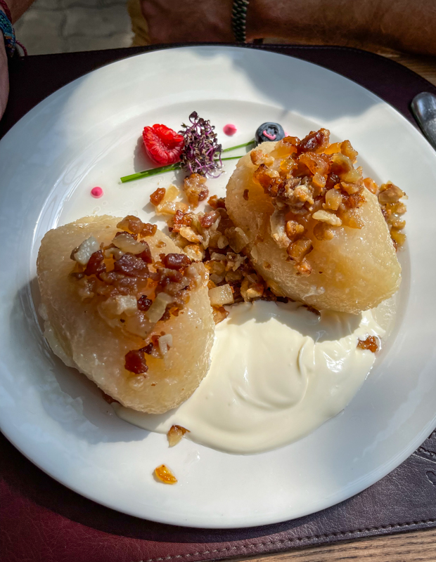 cepelinai or Lithuanian potato balls stuffed with meat topped with bacon and served with cream