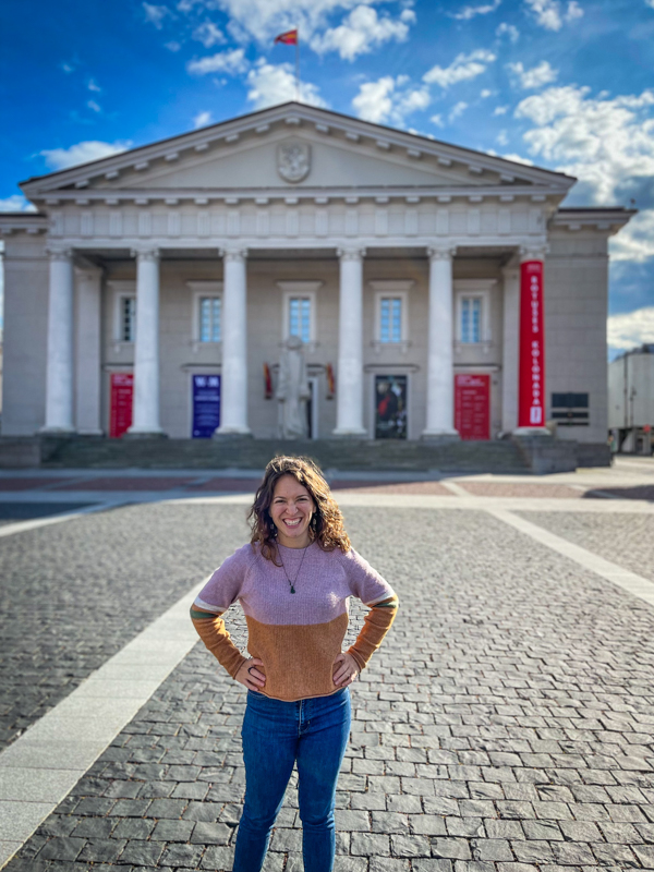 Eternal Expat woman in sweater standing in front of town hall building in vilnius